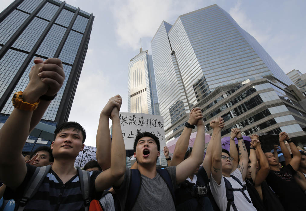 Protesters shout slogans outside a flag-raising ceremony where Hong Kong's embattled leader attended in Hong Kong, Wednesday, Oct. 1, 2014, to mark China's National Day.